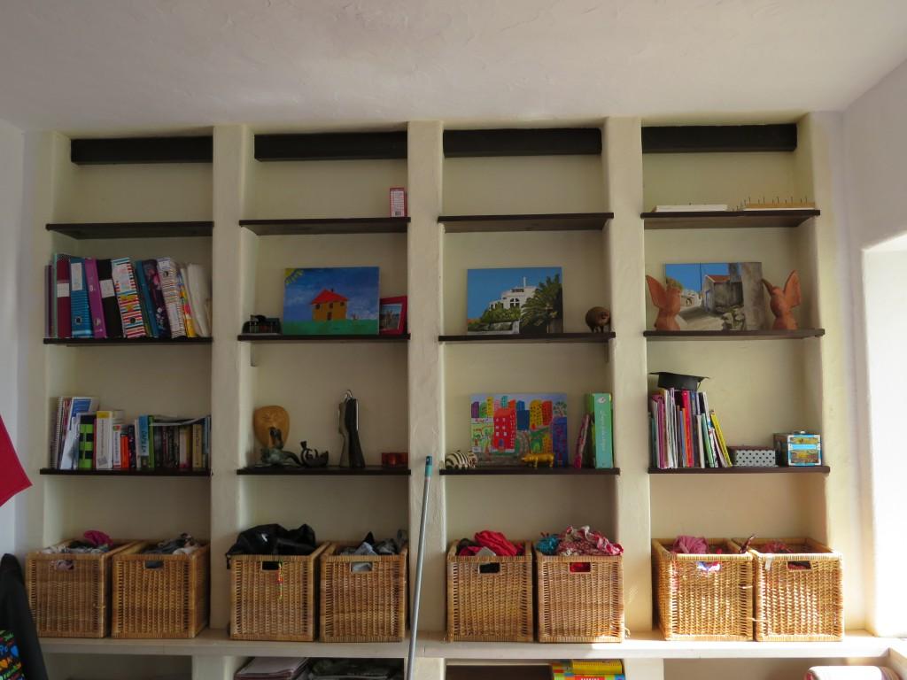 En hel vägg med platsbyggda hyllor utgör en spännande fond som kan varieras i det oändliga. I korgarna som komemr från möbelvaruhuset och som visade sig passa perfekt på millimenterna i hyllan förvaras kläder som är bra att ha till hands. Konstverk spapade av barnen och morfar pryder hyllorna. En kombination av walk-in-closet, galleri och bibliotek.