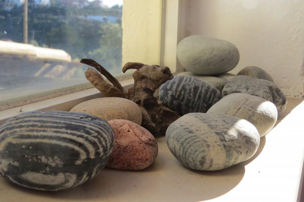 I ett av fönstren har man skapat ett stilleben av stenar från en av de vackra stränderna som finns en kort promenad bort.