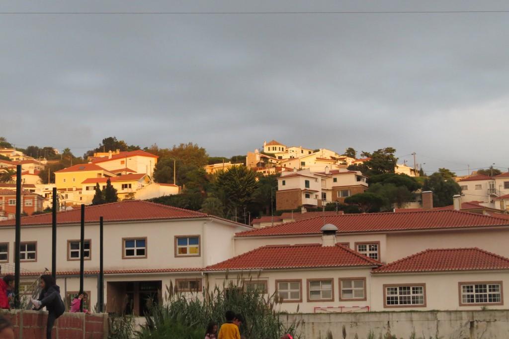 Gammeldagiset i förgrunden och skolan en bit upp på kullen med gula knutar.
